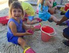 a little girl playing in a sand